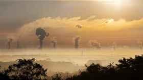 Un paisaje con fábricas emitiendo gases a la atmósfera.