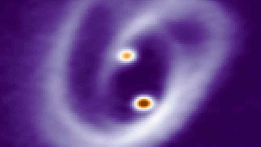 Los complejos filamentos en forma de pretzel que rodean a las dos jóvenes estrellas y a sus pequeños discos.