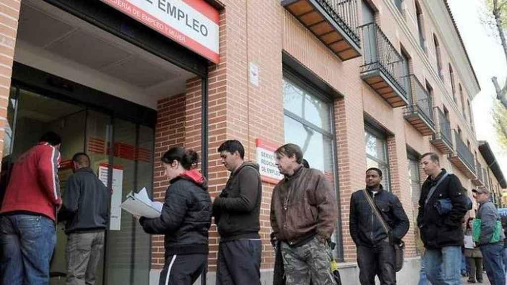 Gente esperando en la puerta de la oficina de empleo.