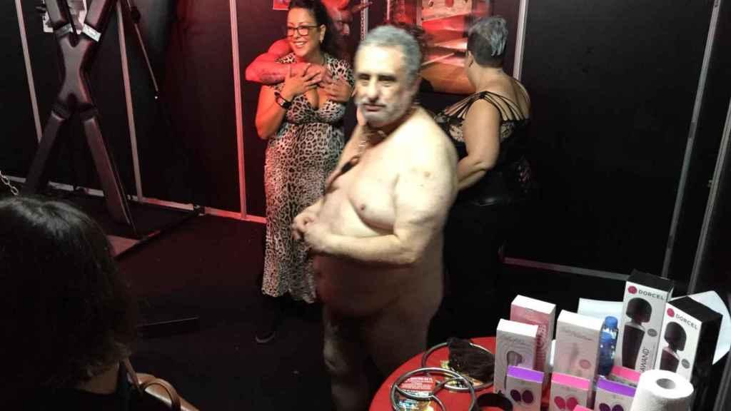 Hombre desnudo con collar de perro en el stand de BDSM