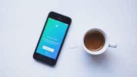 App de Twitter junto a una taza de café.