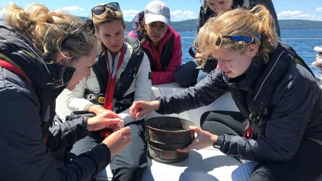 Un grupo de mujeres examina muestras de plástico extraídas del océano en una misión pasada de eXXpedition.