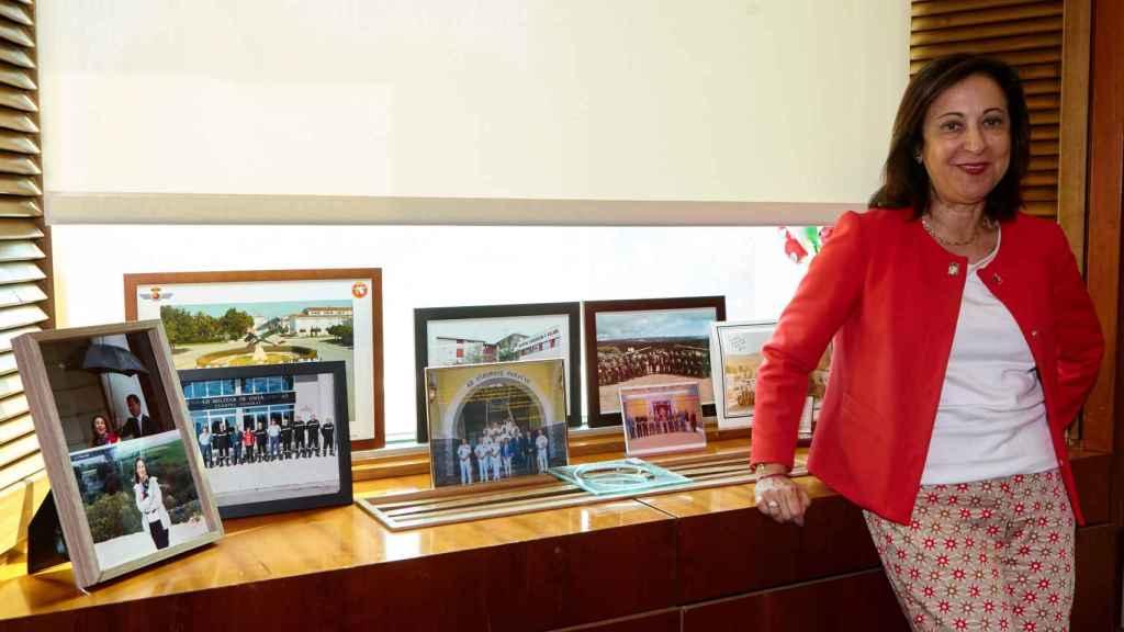 Margarita Robles, en su despacho, junto a varias fotografías en visitas a misiones internacionales.