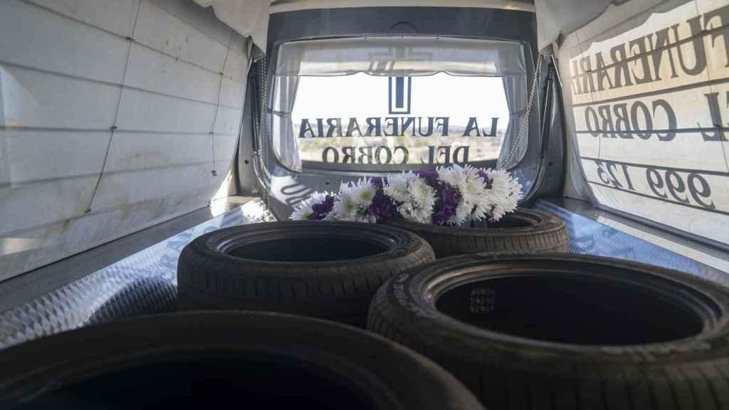 En el interior del coche fúnebre hay una corona de flores y varios recambios de ruedas.