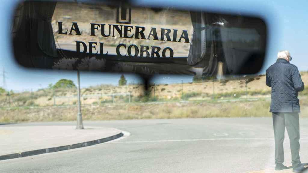 El coche fúnebre está rotulado con cruces y el nombre de la empresa por todas partes.