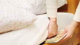 Una persona guarda dinero bajo el colchón.