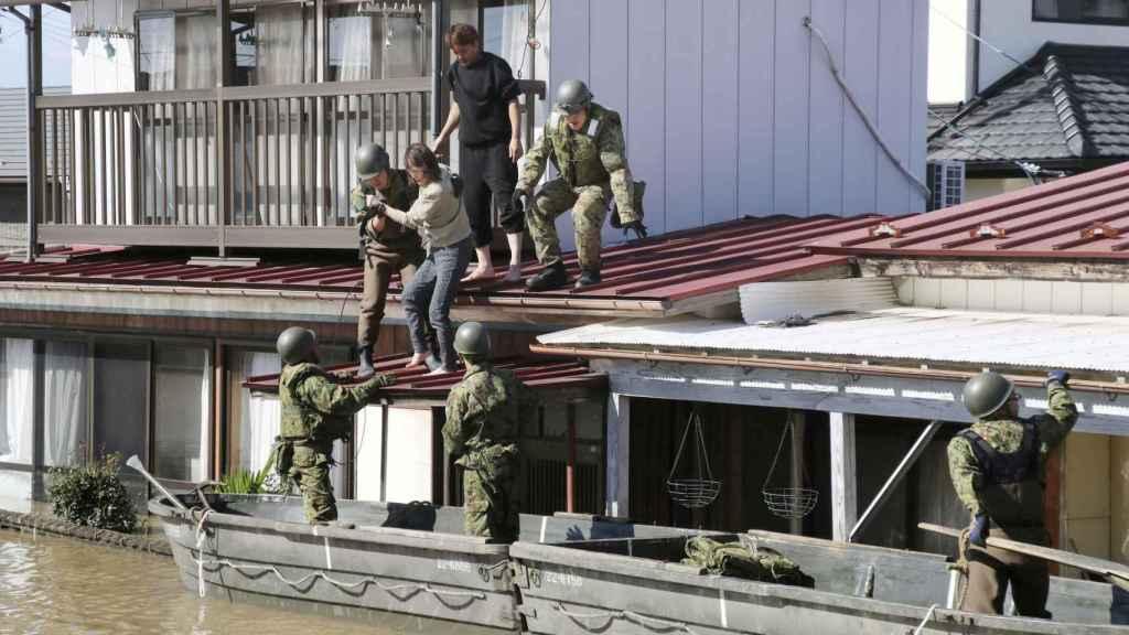 Miembros de los equipos de rescate ayudan a desalojar las viviendas.