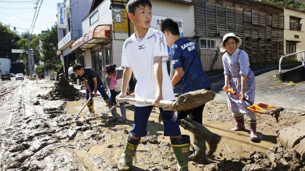 Niños y adultos ayudan a retirar el barro de las calles tras el tifón.