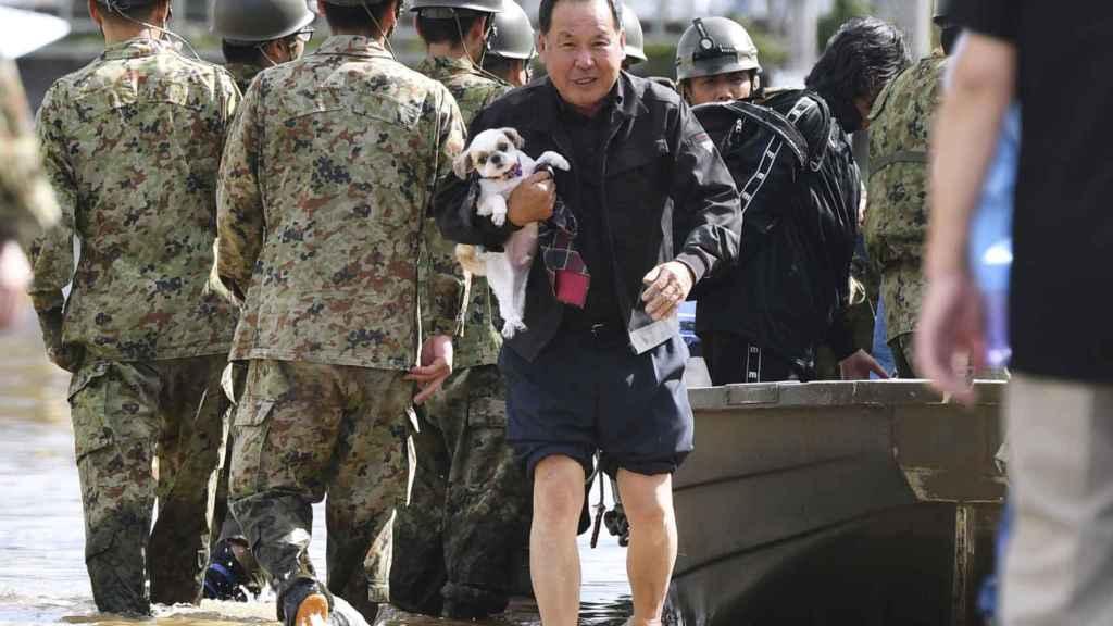 Un hombre con su perro en brazos es evacuado por los servicios de rescate en Motomiya.