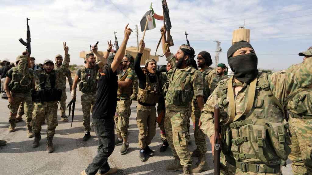 Combatientes rebeldes sirios respaldados por Turquía sostienen sus armas en Tel Abyad.