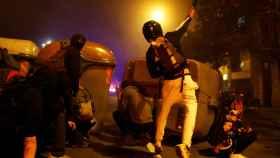 Un grupo de radicales violentos atrincherado detrás de unos contenedores.