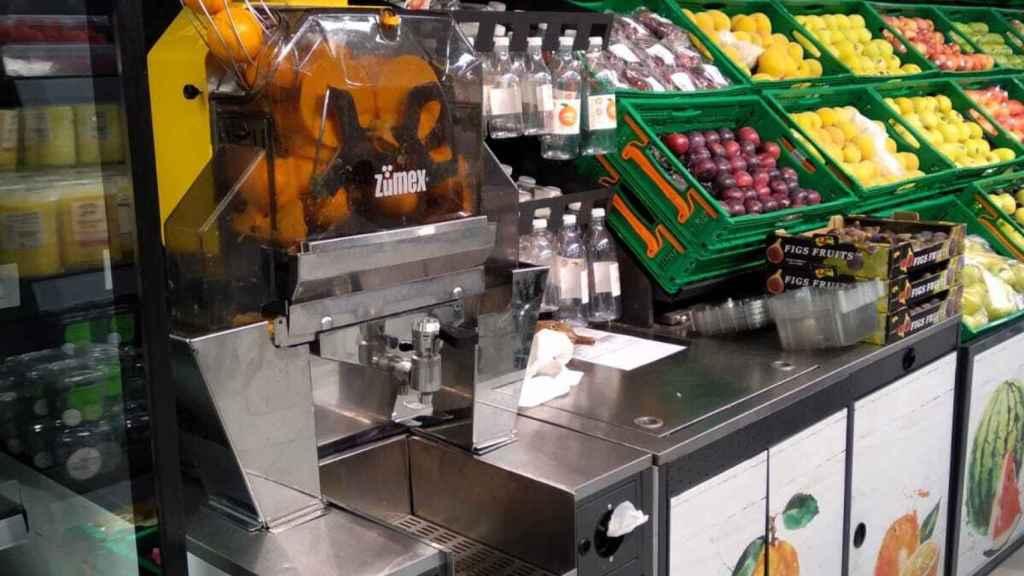 Máquina de zumo y naranjas en la sección de fruta del supermercado.