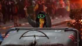 Uno de los radicales separatistas se enfrenta gestualmente a la Policía detrás de unos contenedores