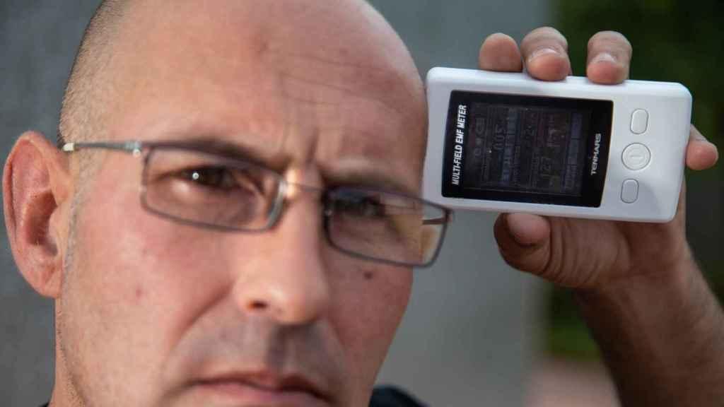 Javier colocando en su cabeza un medidor digital de radiación electromagnética.
