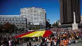 Una enorme bandera de España ha presidido la concentración de Vox en Colón.