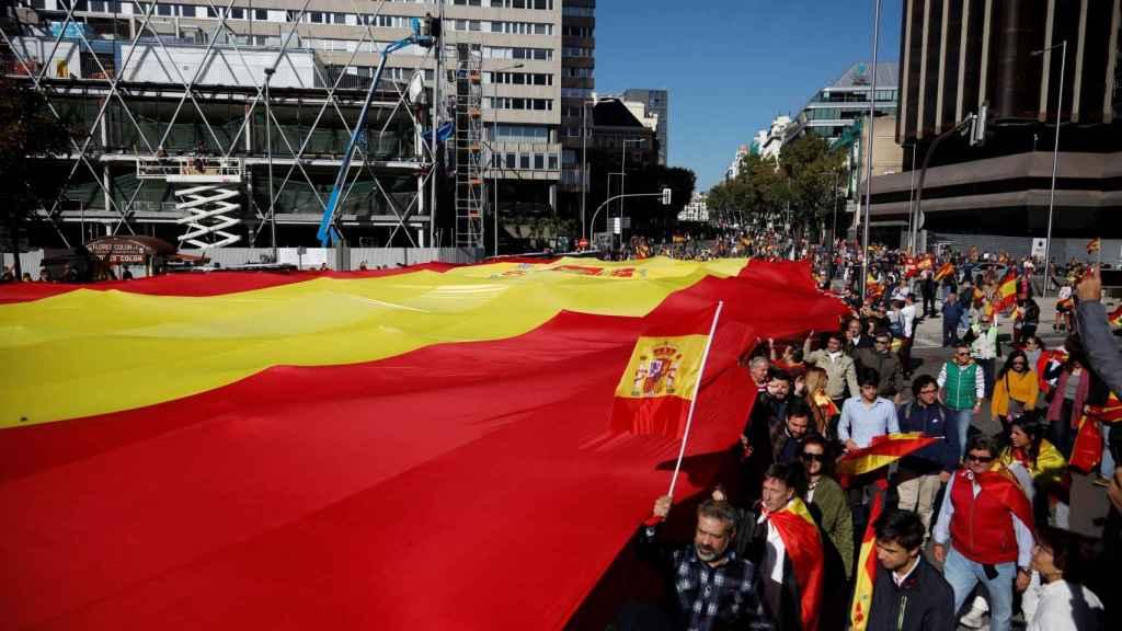 Más de 200 voluntarios sostienen la bandera de España de 1.000 metros cuadrados.