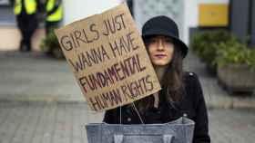 Una joven sostiene un cartel que dice: Las chicas solo quieren derechos fundamentales.