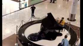 La mujer comenzó a tocar el piano bajo la atenta mirada de varios clientes.