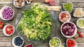 Una mesa repleta de platos con distintas verduras.