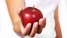 Una mujer sostiene una manzana roja con la mano.