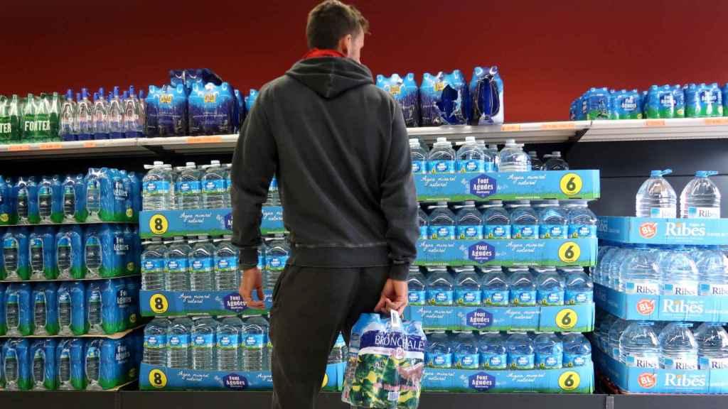 Una hombre escoge una marca de agua embotellada en un supermercado.
