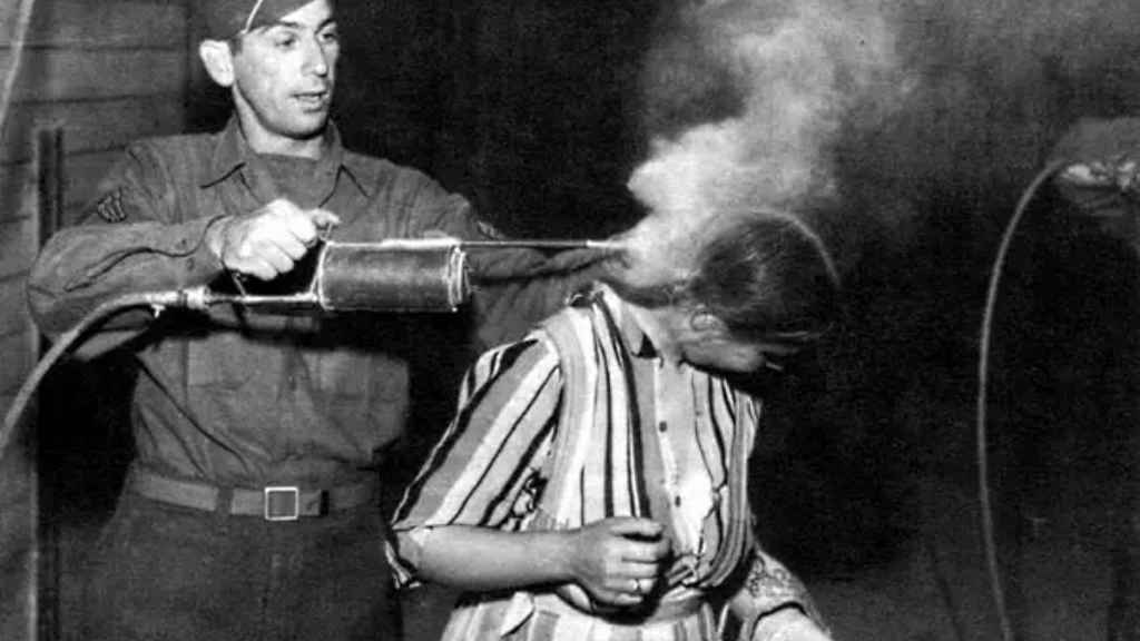 Un soldado estadounidense usando DDT para despiojar a una presa rescatada de un campo de concentración.