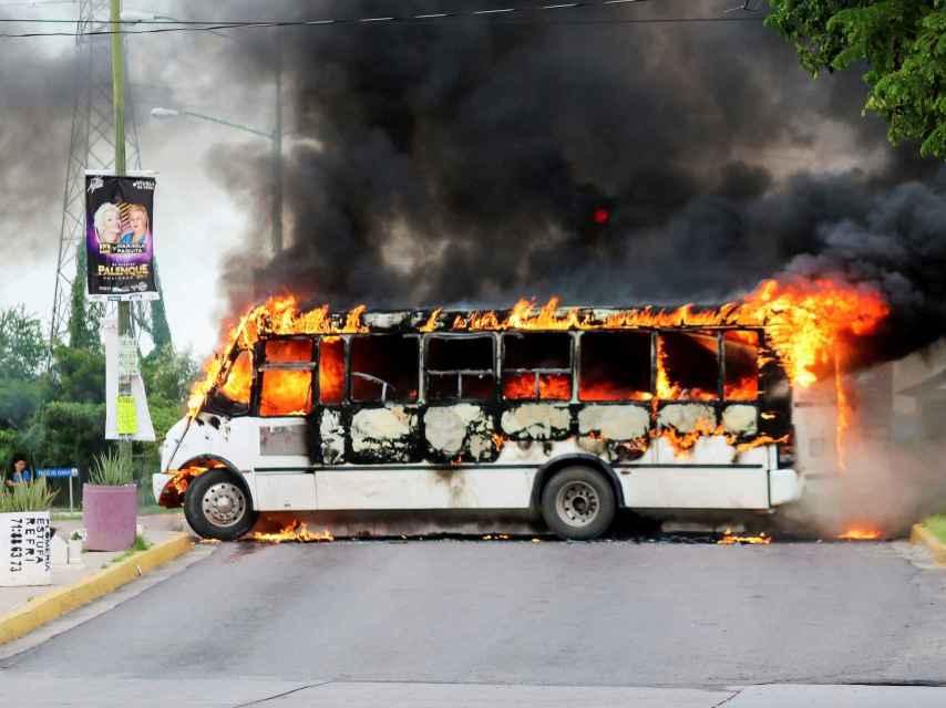 Un autobús ardiendo tras los enfrentamientos entre un cartel y la policía.