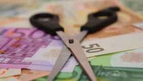 Unas tijeras sobre billetes de euro de distintas denominaciones.