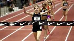 La atleta Mary Cain atraviesa una línea de meta con el logo de Nike.