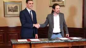 Pedro Sánchez y Pablo Iglesias se estrechan la mano en el Congreso donde han firmado un acuerdo para la formación de un Ejecutivo.