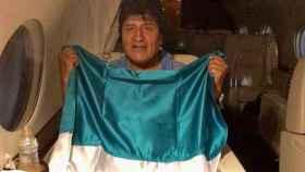 Evo Morales posa con la bandera de Bolivia dentro del avión, camino a México.