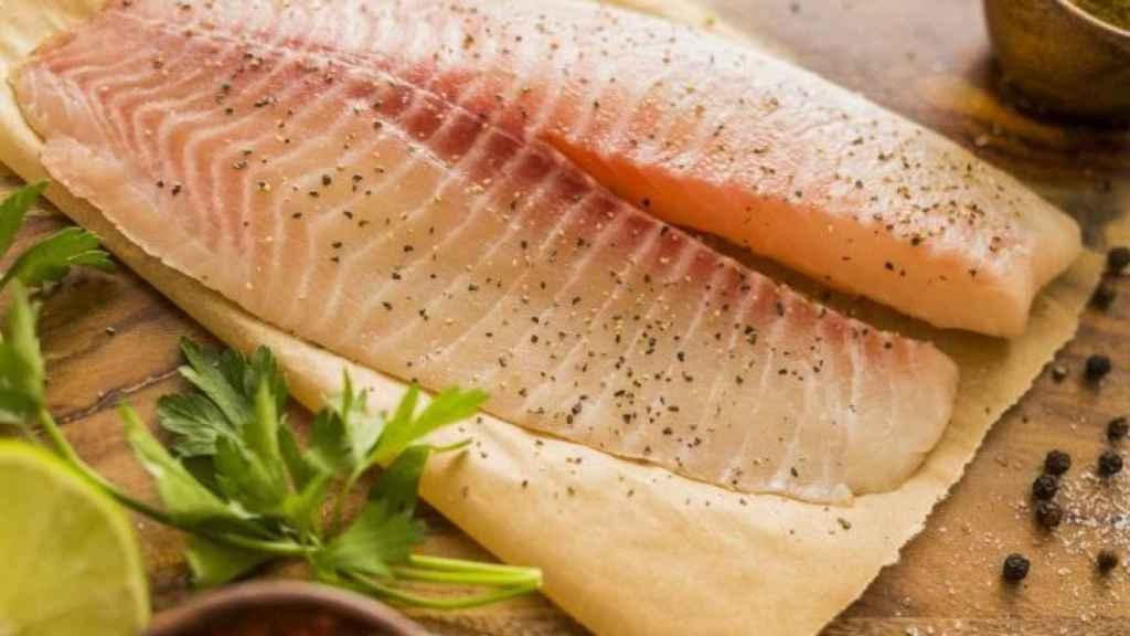 Unos filetes de pescado sobre una tabla de madera.