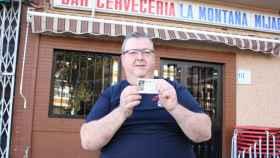 Daniel muestra su décimo de Lotería a las puertas de su bar.