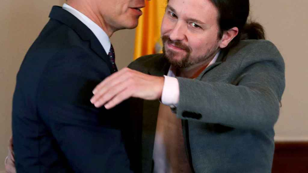 Pedro Sánchez mira de reojo a Pablo Iglesias en el abrazo con el que sellaron su acuerdo de Gobierno de coalición.