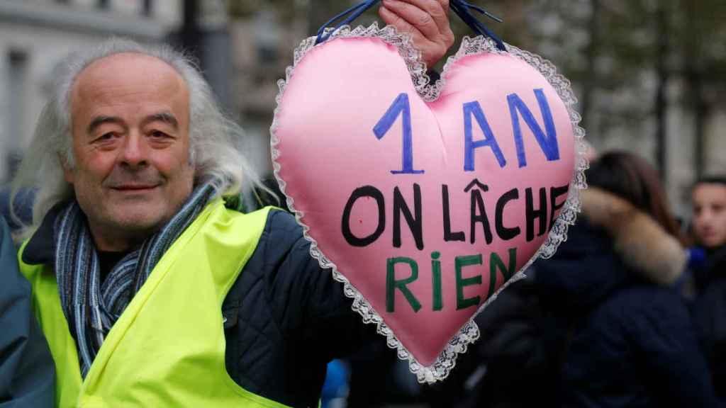 Un manifestante muestra un corazón que conmemora un año de los chalecos amarillos.