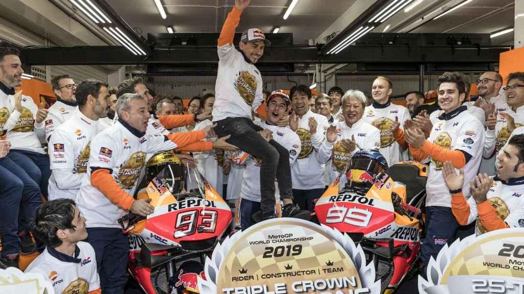 Marc Márquez coge en volandas a Jorge Lorenzo, en el box del equipo Repsol Honda.
