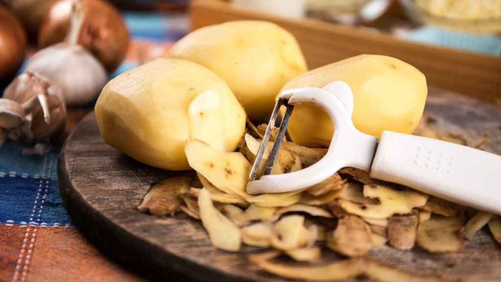 Unas patatas peladas encima de una tabla de madera.