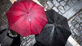 Dos personas pasean por Pamplona bajo sus paraguas.