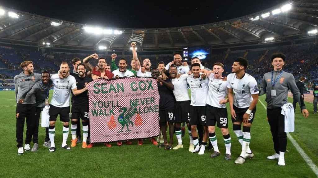 Los jugadores del Liverpool con la pancarta en homenaje a Sean Cox