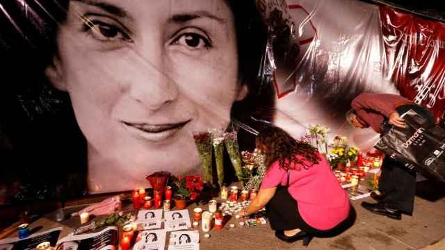 Una mujer pone flores y velas en un monumento a la periodista anticorrupción Daphne Caruana Galizia.