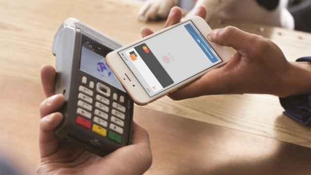 Imagen de archivo de terminal de pago con una tarjeta de Orange Bank en el móvil.