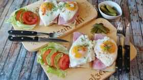 Unas tostadas con huevo, tomate, aguacate y jamón.