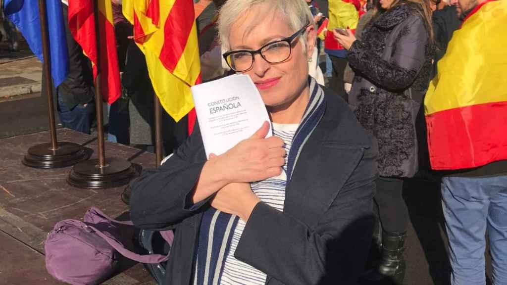 La periodista Anna Grau se abraza a un ejemplar bilingüe de la Constitución.