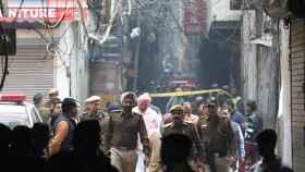 Tres policías caminan entre los escombros de la fábrica que se incendió este domingo en la India.
