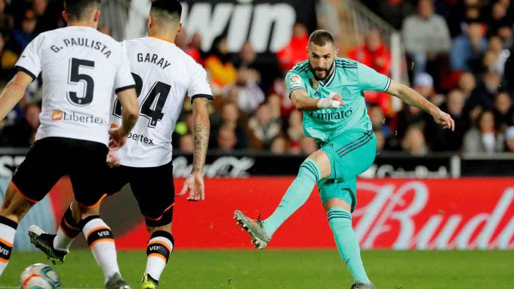 Karim Benzema disparando a portería con varios jugadores del Valencia delante