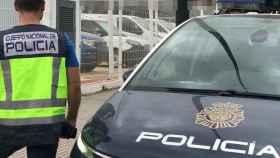 Un agente de Policía Nacional, junto a su coche de intervención.
