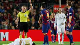 Hernández Hernández muestra la tarjeta amarilla a Luis Suárez