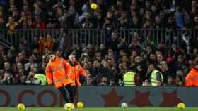 Efectivos de seguridad del Camp Nou intentan sacar del terreno de juego las pelotas amarillas lanzadas desde las gradas