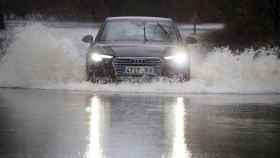 Un coche cruza la carretera LU-P-1701, en Muimenta, Lugo, inundada por el agua de los ríos Pequeño y Miño. EFE/ Eliseo Trigo