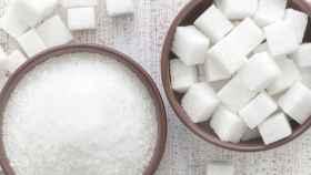 Varios terrones de azúcar junto a un cuenco repleto.